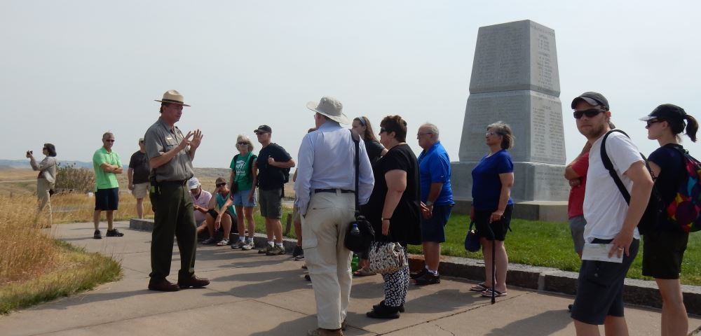 A ranger recounts Custer's last stand at little bighorn next to the 7th Cavalry monument.